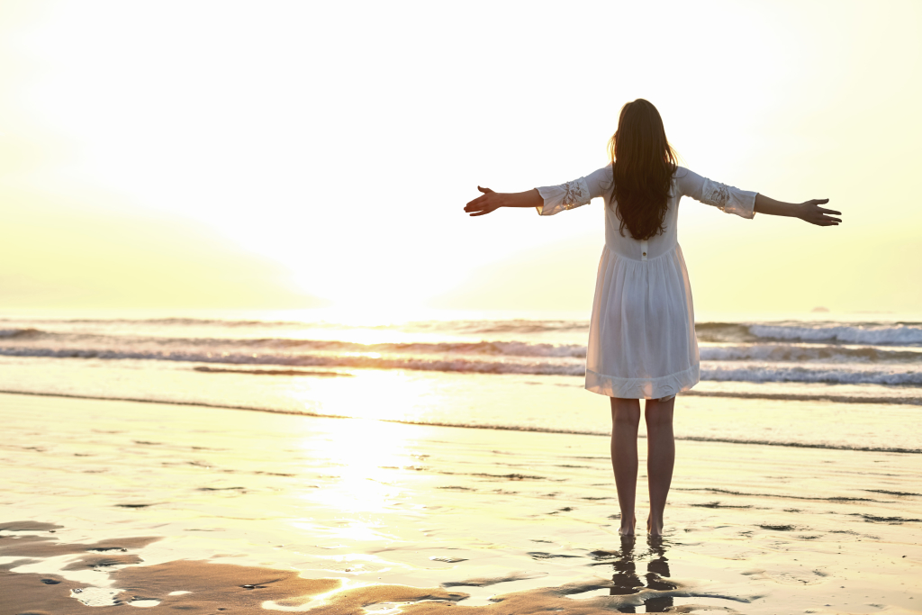 Woman standing arms outstretched on beach during sun
